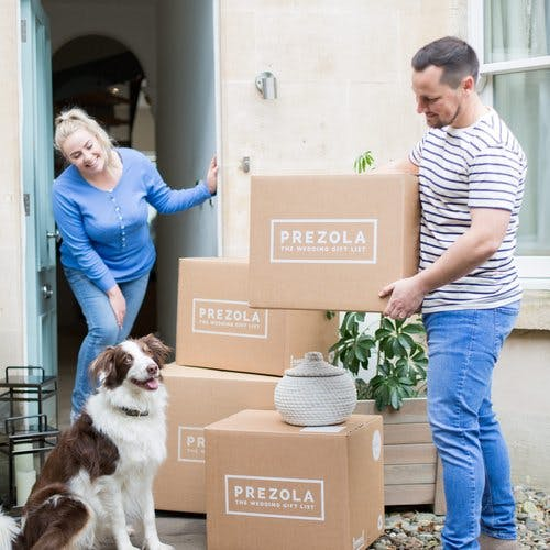 Married couple outside home receiving Prezola delivery of their wedding gifts